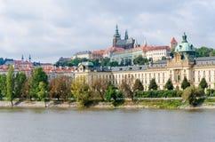 Взгляд на замке Праги от реки Влтавы и на других исторических зданиях мы дерево выровняли идя путь Стоковое Изображение