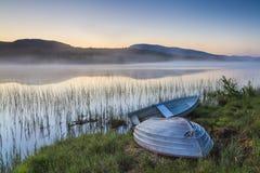 Взгляд на туманном озере с шлюпками на береге Стоковое фото RF