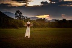 взгляд неба заволакивает на заход солнца с взглядом задней стороны девушки на поле Стоковое фото RF