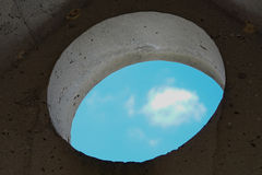 Взгляд неба через круглое отверстие старой каменной стены дома Стоковая Фотография
