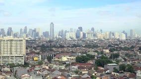Взгляд небольших домов и небоскребов за ими в Джакарте, Индонезии акции видеоматериалы