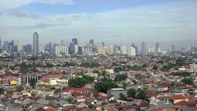 Взгляд небольших домов и небоскребов за ими в Джакарте, Индонезии видеоматериал