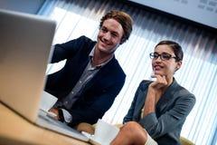 Взгляд низкого угла бизнес-партнера смотря компьтер-книжку Стоковая Фотография RF