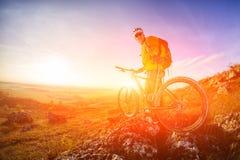 Взгляд низкого угла велосипедиста стоя с горным велосипедом на следе на заходе солнца Стоковые Изображения