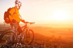 Взгляд низкого угла велосипедиста стоя с горным велосипедом на следе на заходе солнца Стоковое фото RF