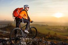 Взгляд низкого угла велосипедиста стоя с горным велосипедом на следе на заходе солнца Стоковая Фотография RF