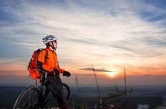 Взгляд низкого угла велосипедиста стоя с горным велосипедом на следе на заходе солнца Стоковое Изображение