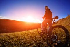 Взгляд низкого угла велосипедиста стоя с горным велосипедом на следе на заходе солнца Стоковая Фотография