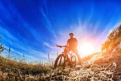 Взгляд низкого угла велосипедиста стоя с горным велосипедом на следе на восходе солнца Стоковое Изображение RF
