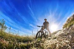Взгляд низкого угла велосипедиста стоя с горным велосипедом на следе на восходе солнца Стоковые Фотографии RF