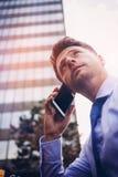 Взгляд низкого угла красивого бизнесмена говоря на мобильном телефоне Стоковое Изображение