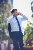 Взгляд низкого угла красивого бизнесмена говоря на мобильном телефоне Стоковые Фотографии RF