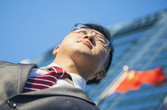 Взгляд низкого угла молодого бизнесмена перед зданием с китайцем сигнализирует на заднем плане стоковая фотография