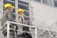 Взгляд низкого угла молодого мужского архитектора при сотрудник обсуждая на лестнице Стоковое Фото