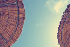 Взгляд низкого угла на 2 парасолях соломы с голубым небом в середине; увяданный, ретро стиль Стоковая Фотография