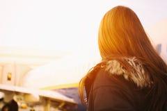 Взгляд низкого угла портрета женщины перед самолетом против неба Стоковое Фото