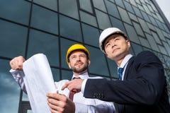 Взгляд низкого угла профессиональных архитекторов в защитных шлемах обсуждая проект Стоковое фото RF