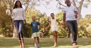 Взгляд низкого угла счастливой семьи держа руки и идти видеоматериал