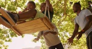 Взгляд низкого угла счастливой семьи играя на качаниях сток-видео