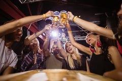 Взгляд низкого угла счастливых друзей провозглашать стекла пива пока сидящ на таблице Стоковые Изображения RF