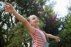 Взгляд низкого угла усмехаясь девушки с оружиями протягивал положение против деревьев Стоковые Изображения