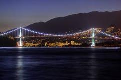Взгляд ночи города, моста, гор, и морской воды стоковое фото rf
