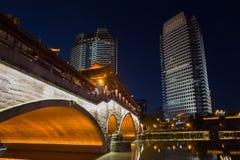 Взгляд ночи красивого моста Anshun над рекой Jinjiang, и центром города Jiuyanqiao в голубом часе стоковые фотографии rf