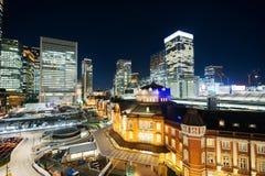 Взгляд ночи панорамного современного глаза птицы горизонта города воздушный с станцией токио под драматическим заревом и красивым Стоковые Фото