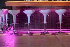 Взгляд ночи стойки бара с уютными белыми декоративными стульями Стоковое Изображение