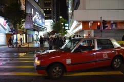 Взгляд ночи улицы Sai Yeung Choi с поворачивая такси на ненастной ноче в Гонконге Стоковые Фото