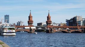 Взгляд оживления реки от моста cke ¼ Schillingbrà при желтый поезд проходя на мост Oberbaum на предпосылке, Берлин стоковое фото rf