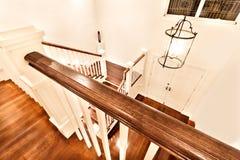 Взгляд лоснистых деревянных лестниц от верхней части показывая закрытую дверь Стоковое Фото