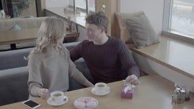 Взгляд от верхней части: парень и девушка сидя на таблице в кафе около окна видеоматериал