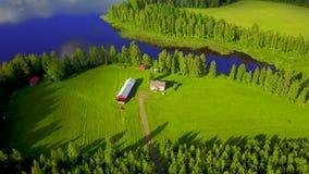 Взгляд от воздуха к мелкому крестьянскому хозяйству на береге красивого озера окруженного лесами видеоматериал