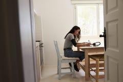 Взгляд от входа девочка-подростка делая домашнюю работу в кухне Стоковые Фото