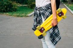 Взгляд от задней части девушки в джинсах, футболке и тапках, которые Стоковые Фотографии RF