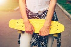 Взгляд от задней части девушки в джинсах, футболке и тапках, которые Стоковое Изображение