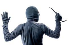 Взгляд от задней части преступника в балаклаве с его руками Стоковое Изображение RF