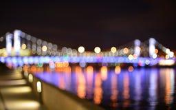 Взгляд от обваловки реки к расплывчатому мосту Krymsky в ноче Стоковое фото RF