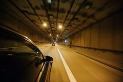 Взгляд от окна автомобиля, автомобиль двигая через тоннель на свете стоковые изображения