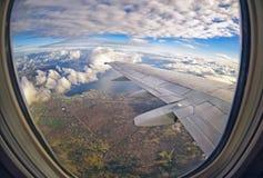 Взгляд от окна самолета на зеленых полях и облаках Стоковое Изображение RF