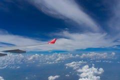 Взгляд от окна самолета показывающ крыло самолета с голубым небом Стоковые Фотографии RF