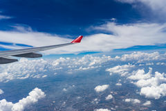 Взгляд от окна самолета показывающ крыло самолета с голубым небом Стоковые Изображения RF