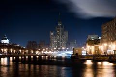 Взгляд от другой стороны реки к пригорку или небоскреба на обваловке Kotelnicheskaya в ноче Стоковые Изображения