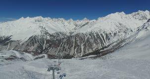 Взгляд от aero к наклону и лыжникам лыжи собирает около подъема лыжи, среди гор в 4K сток-видео