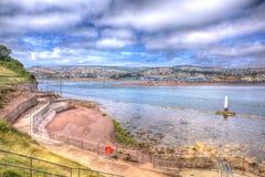 Взгляд от Shaldon к Teignmouth Девону Англии Великобритании в HDR с утесами и ясным морем Стоковые Фото