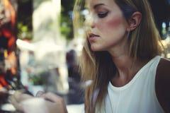 Взгляд однако окно молодой шикарной женщины беседуя на умном телефоне пока сидящ в интерьере бара кафа Стоковые Фотографии RF