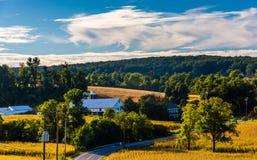 Взгляд проселочной дороги через поля Rolling Hills и фермы внутри Стоковые Изображения