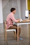 Взгляд профиля бизнесмена работая на компьютере Стоковое Изображение