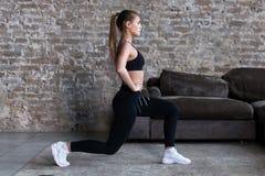 Взгляд профиля sporty девушки делая выпады разрабатывая мышцы и glutes ноги в интерьере просторной квартиры Стоковое Изображение RF